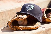 A Charlotte Knights hat sits on top of a glove in the visitor's dugout at Durham Bulls Athletic Park on August 28, 2011 in Durham, North Carolina.   (Brian Westerholt / Four Seam Images)