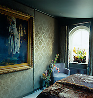 In the bedroom hidden wardrobes have been created behind a large gilt-framed portait displayed on gold-damask covered walls