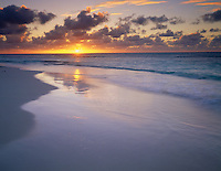 Anguilla, BWI:  Sun setting over the Caribbean waters with reflections on the beach of Lower Shoal Bay (East)