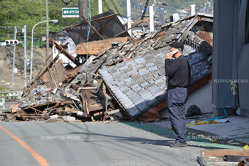 April 17, 2016, Kumamoto, Japan - A man uses his mobile phone before a collapsed house at Mashiki town in Kumamoto prefecture on Sunday, April 17, 2016. More than 40 people died and some 1,000 injured as massive earthquakes attacked Japan's southern island of Kyushu. (Photo by Yoshio Tsunoda/AFLO) LWX -ytd-