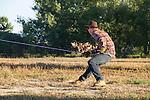 Man pulling on rope and a hot air balloon, Boulder, Colorado, USA.