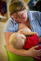 "A woman breastfeeding her little boy at a breastfeeding advice and support drop-in centre.<br /> <br /> Image from the ""We Do It In Public"" documentary photography project collection: <br />  www.breastfeedinginpublic.co.uk<br /> <br /> Hampshire, England, UK<br /> 13/06/2012"