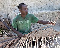 Jambiani, Zanzibar, Tanzania.  Man Weaving a Mat out of Palm Fronds.