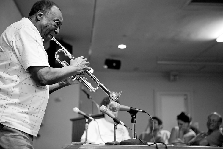 Dave Bartholomew plays some trumpet during his interview at the Ponderosa Stomp's 2nd Annual Music History Conference at the Louisiana State Museum in the Cabildo in New Orleans on April 27, 2009.  <br /> <br /> Dave Bartholomew is a true New Orleans music legend- while he plays the trumpet and was in several bands in the 1940s his true impact on musical culture was felt as a songwriter, composer, and arranger, most notably with Fats Domino.  Collaborating with Fats, the two made more than 40 hits in the 1950s and early 60s, including two number one hits in &quot;Goin' Home&quot; and &quot;Ain't That a Shame&quot;.  Beyond his work with Fats Domino, Bartholomew also wrote songs that were later hits for a variety of artists including Elvis, Chuck Berry, Pat Boone, and Lloyd Price.  In helping define the &quot;New Orleans sound&quot; of the 1950s, Bartholomew was helping define the sound of the new rhythm and blues and rock and roll itself.  He was inducted into the Rock and Roll Hall of Fame in 1991.  <br /> <br /> The Ponderosa Stomp is an annual music festival held in New Orleans since 2002 that celebrates the uncelebrated names in American musical history.  The festival spotlights musicians who have contributed to the American roots musical canon in various genres, from rockabilly to soul to rock and roll to jazz to experimental.  For two nights of the year these mostly forgotten names perform to an audience of aficionados whose memory has not faded and turn back the clock with blistering performances of the hits that did or (in the case of the regional musicians that plugged away unknown to the world at large, as well as those whose songs were recorded to acclaim by other musicians) did not make them famous.