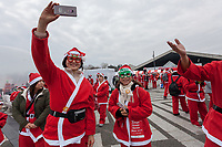 Participants take a selfie before taking part in the Tokyo Great Santa Run in Komazawa-daigaku Olympic Park, Tokyo, Japan. Sunday December 22nd 2019, The great Santa Run was first run in Tokyo in 2018. This years run saw over 3,000 people in Santa costumes run and walk a 4.3 kilometre course to raise money for medical charities in japan and water projects for the Maasai in Kenya.