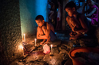 "MANILA, PHILIPPINES - OCTOBER 02: Roel Scott, 13, sits in front of candles lit on the bloodied spot where his uncle, Joselito Rufino Jumaquio, 52, was killed earlier that evening, in the early hours of October 02, 2016 in Manila, Philippines. According to neighbors, at 9pm, at least 15 unidentified plain clothed police wearing masks, descended over the close railway side community quickly and silently. Roel, 13, Joselito's nephew, was playing a videogame with his uncle in small stall when the men grabbed his uncle and handcuffed him. They dragged the powerless pedicab driver towards the alleyway behind the stall and shouted at residents still gathered to go back into their homes and to turn their lights off. The residents then only reported what they heard. A woman's voice shouted ""He's fighting it out,"" or Nanlaban, a term used in many police reports to justify the use of lethal force. Two shots rang out - then 4 more. After the group left, neighbors discovered Joselito's bloodied body, a gun placed next to his handcuffed hands and a white plastic bag with methamphetamine. According to police, this was a legitimate buy bust operation where the handcuffed target drew a .38 calibre handgun and then, ""Sensing that his life was in serious danger, the lawman was constrained to fire back in order to protect his life against the armed aggressor."" After the men left they found Joselito handcuffed and found his body with a gun was placed next to him and a white plastic bag full of narcotics placed on his dead body. Elisa, Joselito's wife, arrived at the scene and started to confront police when she found out the news. Family and friends tried to restrain her but she continued. An angry crowd of residents gathered and started shouting at the police.""We curse you,"" they yelled, citing the countless times those arrested have been killed on the grounds that they were fighting back. ""You have no pity. We are poor, and we are alone. We hope we can find allies.�"