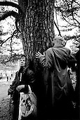 Kirov (Vyatka) Region, Russia  .1998.Pilgrims who have reached the river pray against a holy tree that is close to where the famous icon was found some 600 years ago. The original was lost during the communist era and a replica is now carried in its place during the three-day pilgrimage..