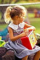 Young girl with lunch pail waiting for a ride after school