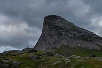 Silhouette of female hiker with Segltind mountain peak in background, Moskenesøy, Lofoten Islands, Norway