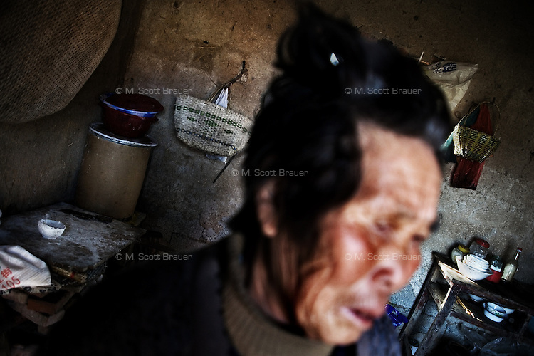 Wang Bao Ying, frequently ill and over 75, cries in her home as she describes the life of her orphan grandchild Fan Lu Yang, 10, in Fanzhuang Village, Jiangsu Province, China.  The boy's father died in 2000 in a coal mining accident and his mother, affected by dementia, wandered away and disappeared a year before this picture was taken.  The boy's guardians cannot provide financial or material support for the boy and fear what will happen to him when they pass away.  At the time of the picture, China's Amity Foundation charity, was investigating the family's situation in preparation to raise money to financially support these children and other orphans in similar situations.  With Amity's support, each orphan, aged 6-12, would receive approximately 1,400 RMB annually (about 200 USD) to pay for the cost of living. Amity works to keep children out of the institutional orphanages in China, preferring to provide monetary assistance that can help maintain a family environment for the orphans it helps.