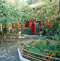 The cobbled courtyard approach to the house has been planted with beds of flowers and bamboo