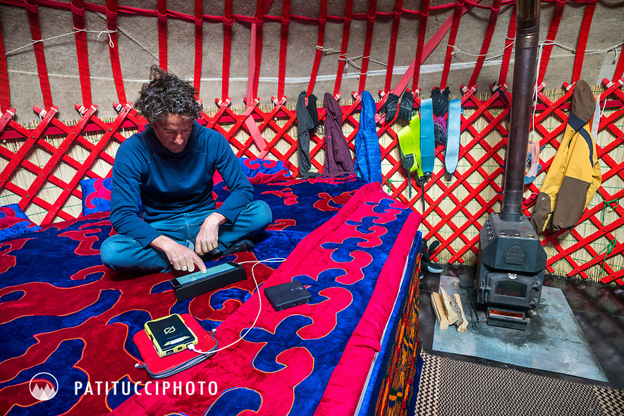 A man sits inside a yurt using an iPad and battery pack while traveling in Kyrgyzstan
