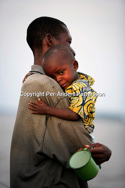 LISALA, DEMOCRATIC REPUBLIC OF CONGO APRIL 1: An unidentified man comforts his son as they just woke up early in the morning on a boat on April 1, 2006 in Lisala, Congo, DRC. They are traveling from Kisangani to Kinshasa, a journey of about 1750 kilometers. The boat stopped for a week in Lisala to load maize bags and more passengers. The Congo River is a lifeline for millions of people, who depend on it for transport and trade. Passengers usually sleep in the open, often on top of maize bags or other cargo. The boat carries many animals such as pigs, goats, crocodiles, monkeys, lizards, etc. During the Mobuto era, big boats run by the state company ONATRA dominated the river. These boats had cabins and restaurants etc. All the boats are now private and are mainly barges that transport goods. The crews sell tickets to passengers who travel in very bad conditions, mixing passengers with animals, goods and only about two toilets for five hundred passengers. The conditions on the boats often resemble conditions in a refugee camp. Congo is planning to hold general elections by July 2006, the first democratic elections in forty years. (Photo by Per-Anders Pettersson).