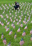 "Photo by Phil Grout..Firefighter/EMT Shelli Click of Howard County Station 2 in Ellicott City repairs one of thousands of American flags which were planted along Little Patuxent Parkway in Columbia to honor the victims of the ""9/11"" attack on American ten years ago."