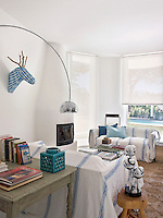 A chrome 1960's table lamp and arc floor lamp in the living room with a pair of sofas covered in blue and white striped throws