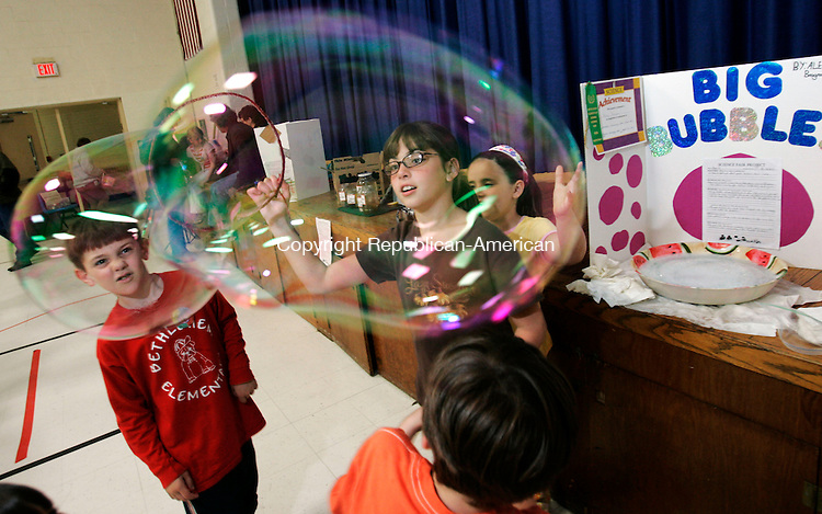 BETHLEHEM, CT 4/25/07- 042507BZ04- Alexa Brogna, 9, gr. 3, center, demonstrates her project by making a big bubble as T.J. Hokunson, 7, gr. 1, of Woodbury, left, Danah Kern, 7, gr. 2, of Bethlehem, behind Brogna, and Aiden Leonard, 7, gr. 1, of Woodbury, foreground, look on during a science fair at Bethlehem Elementary School Wednesday night.<br /> Jamison C. Bazinet Republican-American