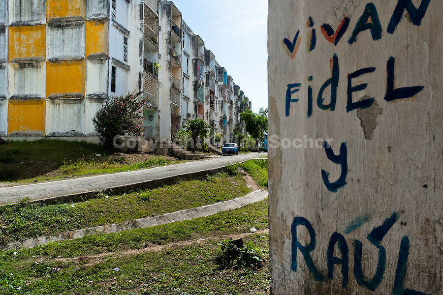 """A propaganda writing is seen on the wall in front of the large apartment block in Abel Santamaría, a public housing periphery of Santiago de Cuba, Cuba, 31 July 2008. The Cuban economic transformation (after the revolution in 1959) has changed the housing status in Cuba from a consumer commodity into a social right. In 1970s, to overcome the serious housing shortage, the Cuban state took over the Soviet Union concept of social housing. Using prefabricated panel factories, donated to Cuba by Soviets, huge public housing complexes have risen in the outskirts of Cuban towns. Although these mass housing settlements provided habitation to many families, they often lack infrastructure, culture, shops, services and well-maintained public spaces. Many local residents have no feeling of belonging and inspite of living on a tropical island, they claim to be """"living in Siberia""""."""