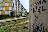 "A propaganda writing is seen on the wall in front of the large apartment block in Abel Santamaría, a public housing periphery of Santiago de Cuba, Cuba, 31 July 2008. The Cuban economic transformation (after the revolution in 1959) has changed the housing status in Cuba from a consumer commodity into a social right. In 1970s, to overcome the serious housing shortage, the Cuban state took over the Soviet Union concept of social housing. Using prefabricated panel factories, donated to Cuba by Soviets, huge public housing complexes have risen in the outskirts of Cuban towns. Although these mass housing settlements provided habitation to many families, they often lack infrastructure, culture, shops, services and well-maintained public spaces. Many local residents have no feeling of belonging and inspite of living on a tropical island, they claim to be ""living in Siberia""."