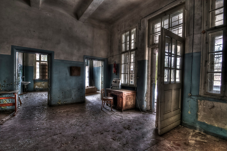 Abandoned lunatic asylum north of Berlin, Germany. Empty room with open doors.