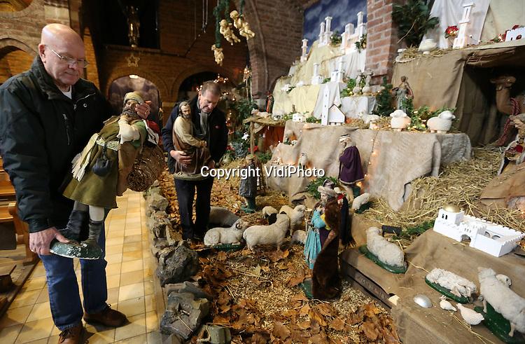 Foto: VidiPhoto<br /> <br /> HUISSEN - In de kerk Martelaren van Gorcum in Huissen-Zand wordt maandag de laatste hand gelegd aan de grootste kerststal van Gelderland en mogelijk zelfs van Nederland. &quot;Jeruzalem in het klein&quot;, noemen bouwers koster Albert Hendriks en misdienaar Wim Damen het tafereel, dat 16 bij 4,5 meter groot is. Ieder jaar wordt de stal groter. Dit jaar komt er zelfs een wensvijver, waar vissen in zwemmen en waarin bezoekers een muntje kunnen gooien. De parochie hoopt zoveel bezoekers te trekken dat sluiting van de kerk in januari 2015 voorkomen kan worden.