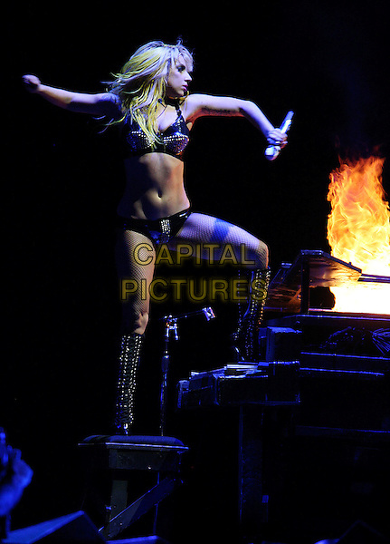 LADY GAGA (Stefani Joanne Angelina Germanotta).Lady Gaga performs in concert at Staples Center in Los Angeles, California on August 11, 2010..music concert gig on stage live .full length black bikini knickers bra silver studs studded microphone yellow hair wig  pvc fishnet tights  hands piano fire burning  boots leg up standing on arm .CAP/ROT/TM.©Tony Michaels/Roth Stock/Capital Pictures