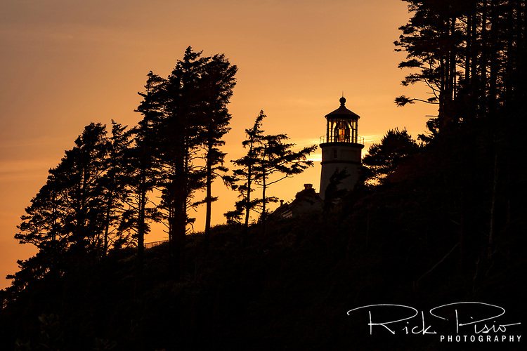 The sun sets to the west of the Haceta Head Lighthouse along Oregon's Central Coast north of Florence.