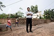 young children run past P K Pattanayak, Chief (IR and R&R) TATA Steel Ltd. while he poses for a portrait in a rehabilitation colony in Kalinganagar, Orissa, India.
