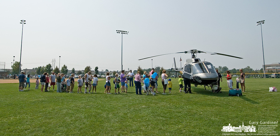 Children and their parents line up to see the inside of the Ohio State Patrol helicopter at the Cops and Kids Day at Hoff Woods Park in Westerville, Ohio.<br />