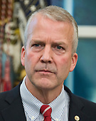 """United States Senator Dan Sullivan (Republican of Alaska) listens as US President Donald J. Trump makes remarks prior to signing S. 3508, the """"Save Our Seas Act of 2018"""" in the Oval Office of the White House in Washington, DC on Thursday, October 11, 2018.  <br /> Credit: Ron Sachs / CNP"""