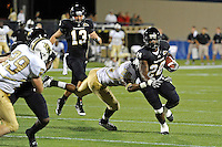 17 September 2011:  FIU running back Darriet Perry (28) attempts to break away from UCF defensive back Clayton Geathers (26) while carrying the ball in the second half as the FIU Golden Panthers defeated the University of Central Florida Golden Knights, 17-10, at FIU Stadium in Miami, Florida.