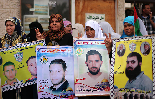 Palestinians hold pictures of prisoners held in Israeli jails, during a protest, in front of Red cross office, in Gaza city, on May 11, 2015. Photo by Ashraf Amra