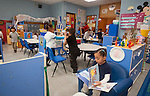 WATERBURY,  CT-122216JS03- Children enjoy other activities while Liannys Ruiz, 4, center, reads a book during on Thursday inside Angelina Irizarry's classroom at Sprague Elementary School in Waterbury. The school district is making more seats available to three-year-olds in half-day programs at Sprague and Walsh schools.  Jim Shannon Republican American
