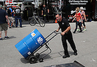 Apr. 26, 2013; Baytown, TX, USA: NHRA crew member for top fuel dragster driver Steve Torrence moves a 55 gallon barrel of VP nitro fuel during qualifying for the Spring Nationals at Royal Purple Raceway. Mandatory Credit: Mark J. Rebilas-