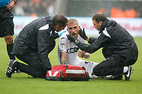 Oli McBurnie of Swansea City (C) is seen to by Dr. Jez McCluskey, Club Doctor(L)   and Physiotherapist, Ritson Lloyd (R) after suffering an injury during the Sky Bet Championship match between Swansea City and Preston North End at the Liberty Stadium, Swansea, Wales, UK. Saturday 11 August 2018