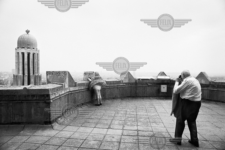 A man taking a picture of his wife, whose skirt is being lifted by the wind, on top of the roof of the Basilica of the Sacred Heart.