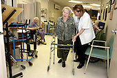 "Sylvia Rubin waits her turn as Esther Snow walks with physical therapist, Pam Sanders on Thursday February 17, 2005. Rubin and Snow are patients at the Greenwood House Home for the Jewish Aged in Ewing, New Jersey. ....The Greenwood House is 70% medicaid. To make up the $500,000 deficit each year incured by medicaid, the Greenwood House raises funds by donations, galas and last year, Pres. Clinton came to New Jersey. ""It's a scramble each year"", says Greenwood House director, Rick Goldstein, ""but it's worth it to provide extra care for the 169 beds we have"". Jane Therese/Sipa"