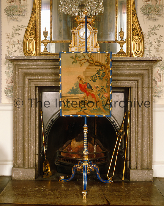 An antique tapestry of a bird in a blue and gold frame is used as a firescreen