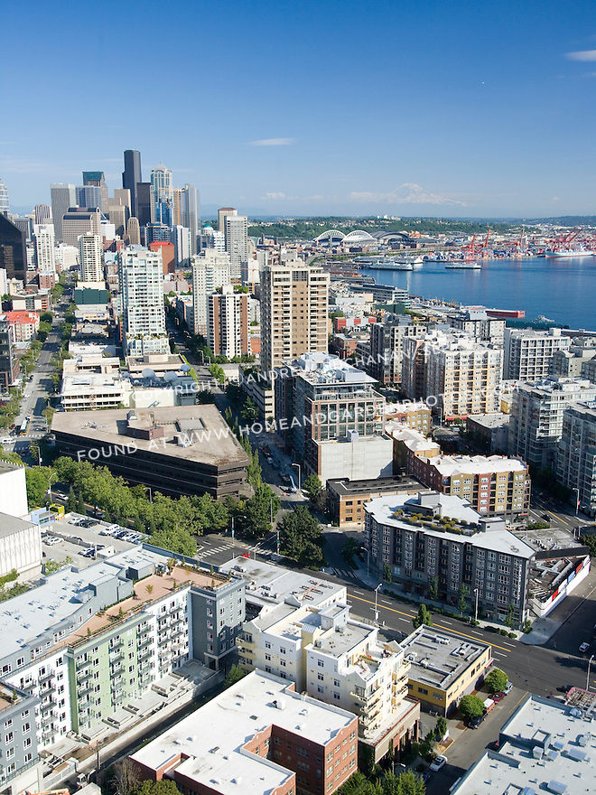A sunny, summer afternoon aerial photo of Seattle, Washington's Belltown / Denny Triangle neighborhood showing skyscrapers of the downtown Seattle skyline next to Elliott Bay, the orange cranes of the Port of Seattle behind, and snow-capped Mount Rainer in the distance.