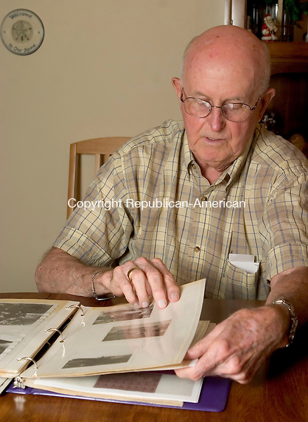 WATERBURY, CT--28 JUNE 2007--062807JS03-Rev. Charles Lanham, a WWII veteran, flips through a scrapbook in his Waterbury apartment. Lanham is one of the millions of people across the country who was born on July 4.<br /> Jim Shannon/Republican-American