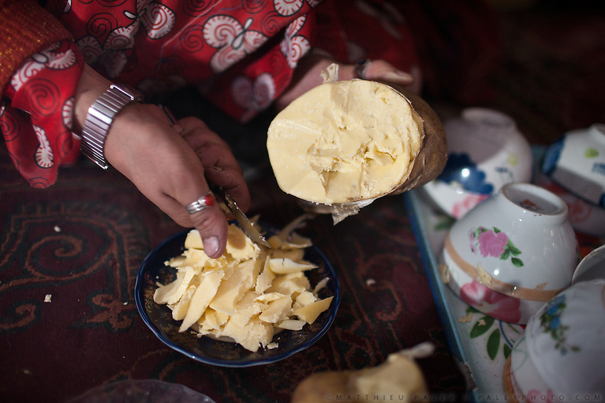 "Cutting pieces of ""Muskat"", a type of butter that is kept inside the sheep's stomach. ""Rokhoon"" is the oil..Kyzyl Qorum, campment of the former deceased Khan, Abdul Rashid Khan...Trekking with yak caravan through the Little Pamir where the Afghan Kyrgyz community live all year, on the borders of China, Tajikistan and Pakistan."