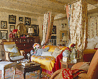 A yellow and red Chinese export hanging is used to cover a sofa in this chintz bedroom