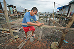 "A man works constructing a new house amid the rubble of his old dwelling in Tacloban, a city in the Philippines province of Leyte that was hit hard by Typhoon Haiyan in November 2013. The storm was known locally as Yolanda. The man's house lies within a controversial 40 meter ""no build"" zone that prohibits such construction. The ACT Alliance has been active here and in affected communities throughout the region helping survivors to rebuild their homes and recover their livelihoods."