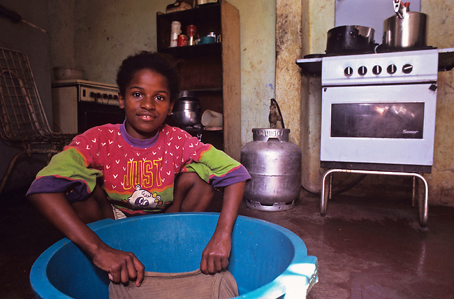 Bresil, Rio de Janeiro. Favela Chacara do Creu, jeune fille lavant le sol de la maison. *** Brazil, Rio de Janeiro, Chacara do Creu favela. Young girl washing the floor.