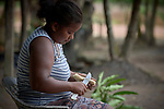 Veronica de Oliveira peels cassava outside her family's home in Quilombo Bom Jardim, near Santarem, Brazil.
