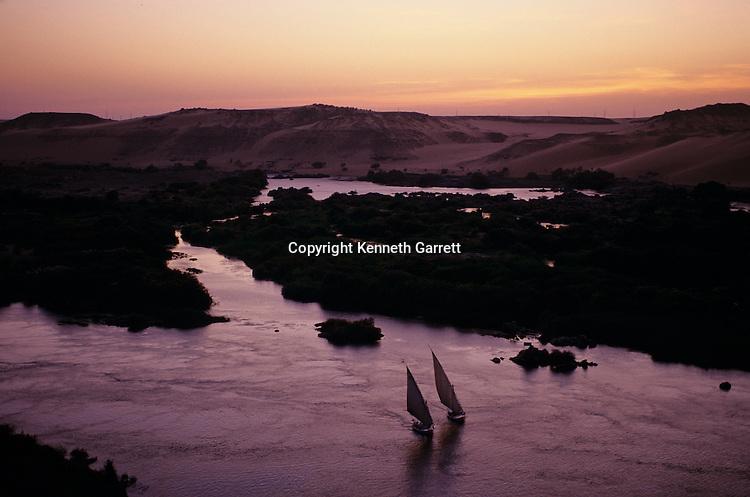 Feluccas sailing at sunset near dammed First Cataract, Aswan, Egypt