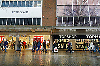 Last minute Christmas shoppers walk past huge 50% and 60% sale signs outside River Island and Topshop stores in Oxford Street, in the city centre of Swansea, Wales, UK. Sunday 24 December 2017