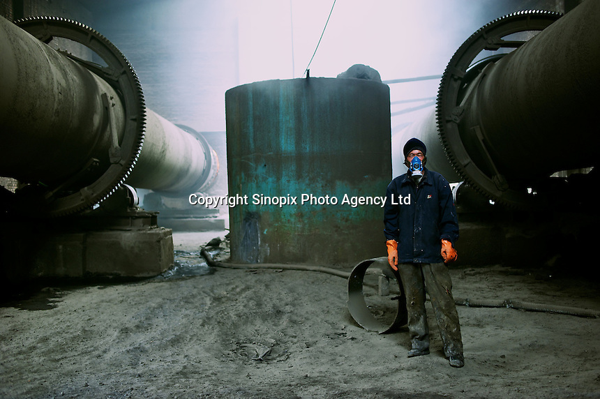 """A worker, his trousers already burnt and full of holes, at  a""""rare-earth"""" processing plant near Bayon Obo, Inner Mongolia.  The plant conducts first stage processing in extremely toxic conditions where workers complain of acid burns and sores as well as head-aches. The production of """"rare-earths"""" is an extremely poisenous process with plants in the U.S. being closed due to environmental concerns. China accounts for some 97% of rare earth consumed world-wide. The """"rare earth elements"""" are a group of 17 elements that are essential in 25% of modern technology including cell phones, computer hard discs, and electric motors and inparticular green technology such as electric batteries and wind turbines."""