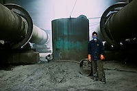"A worker, his trousers already burnt and full of holes, at  a""rare-earth"" processing plant near Bayon Obo, Inner Mongolia.  The plant conducts first stage processing in extremely toxic conditions where workers complain of acid burns and sores as well as head-aches. The production of ""rare-earths"" is an extremely poisenous process with plants in the U.S. being closed due to environmental concerns. China accounts for some 97% of rare earth consumed world-wide. The ""rare earth elements"" are a group of 17 elements that are essential in 25% of modern technology including cell phones, computer hard discs, and electric motors and inparticular green technology such as electric batteries and wind turbines."