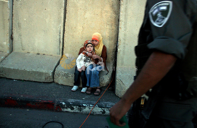 Palestinian children wait for other family members to go through security checks to cross into Jerusalem from Israel's Qalandiya checkpoint outside the West Bank city of Ramallah, during the third Friday of the holy month of Ramadan August 19, 2011.  Photo by Issam Rimawi