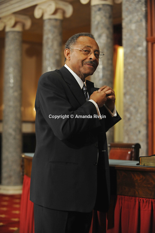 Senator Roland Burris puts on his members' pin in the old Senate chamber of the U.S. Senate in Washington, DC on January 15, 2008.
